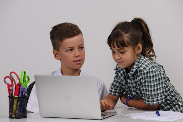 Boy and girl working on computer dressed in school uniform
