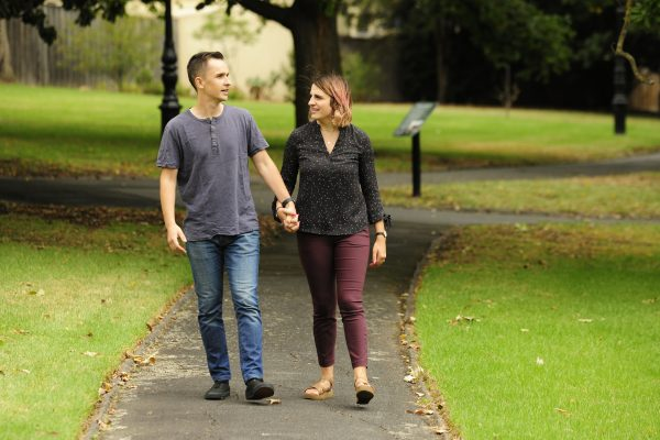 Young man and woman walking in park holding hands