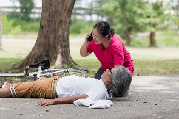 Woman helping man fallen on off bike