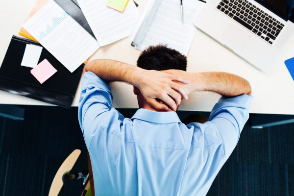 Man slumped over desk with hands on head