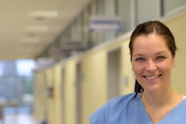 Smiling nurse in hospital corridor